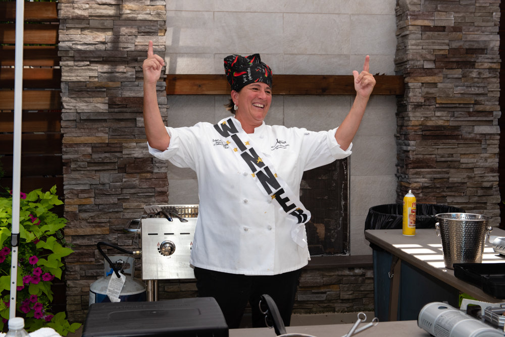 Lori Cavuoti, head chef at Atria Riverdale, raises her arms victoriously at the end of the senior living facility's annual Chef Showdown. Cavuoti whipped up meatballs, chicken wings and pizzas, with peppers as the central ingredient.