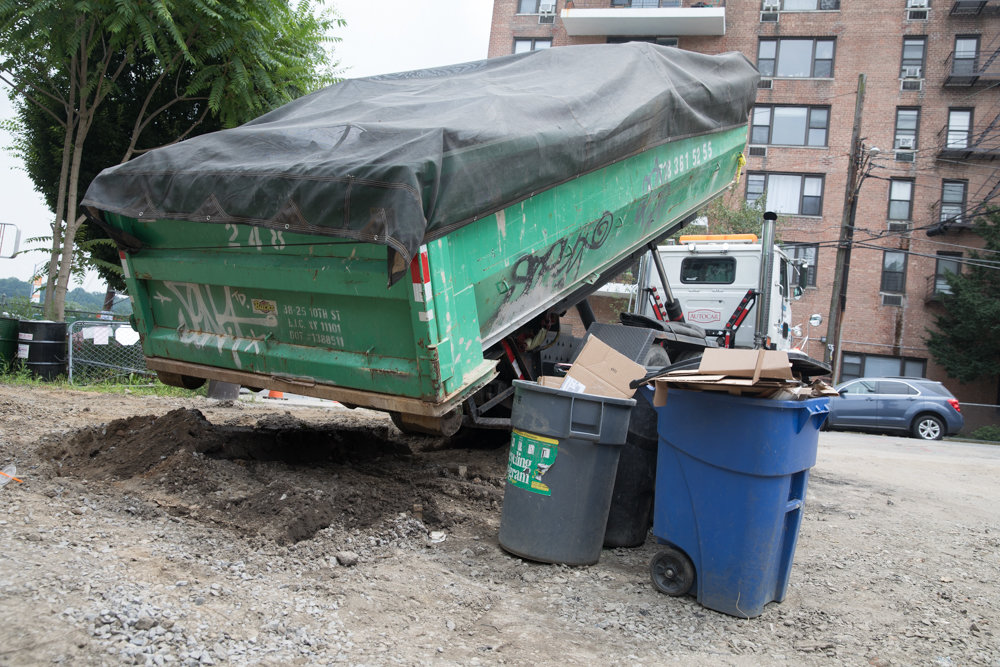A dumpster full of detritus is removed from Old Albany Post Road, a ramshackle stretch of land between Broadway and Post Road. In January, local elected officials called attention to the road, which is owned by the state, an entity that has done little — if anything — to improve it.