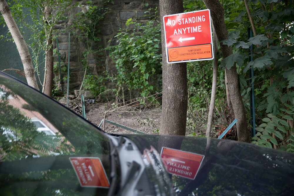 A 'no standing anytime' sign is reflected on the hood of a car parked along Old Albany Post Road where there is ongoing construction on a residential building. Neighbors along the road have called 311 incessantly with complaints about the state-owned stretch of land, which often has been prone to flooding.