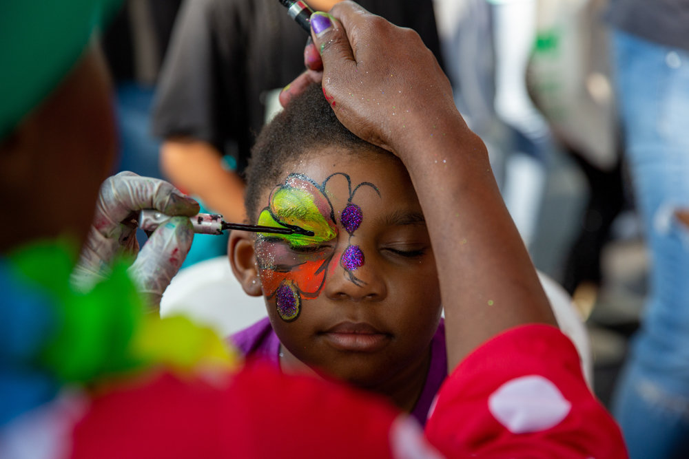 Yvonne Cerque paints a flower on Tatiana Small's face during National Night Out, a nationwide community-building event for police precincts. The 5-0 held its event on West 234th Street between Bailey Avenue and Broadway.