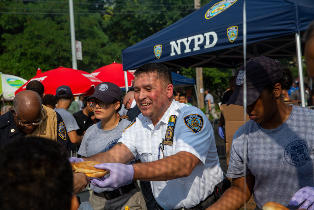 Capt. Emilio Melendez hands out burgers and hot dogs to attendee's of the 50th Precinct's National Night Out on West 234th Street between Bailey Avenue and Broadway.