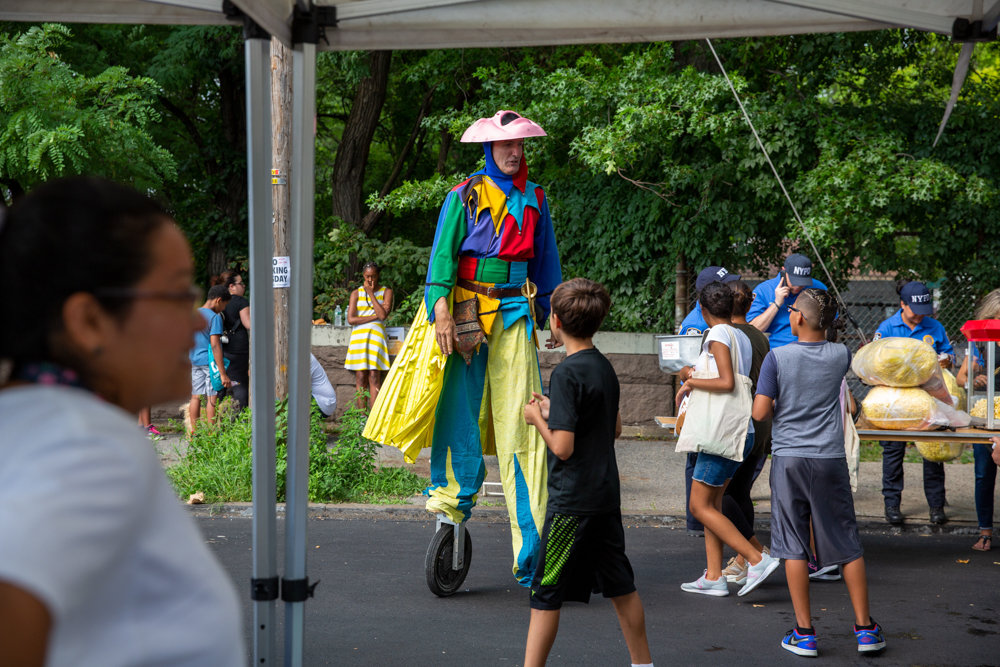A jester on stilts and wheels entertains the crowd during the 50th Precinct's National Night Out event.