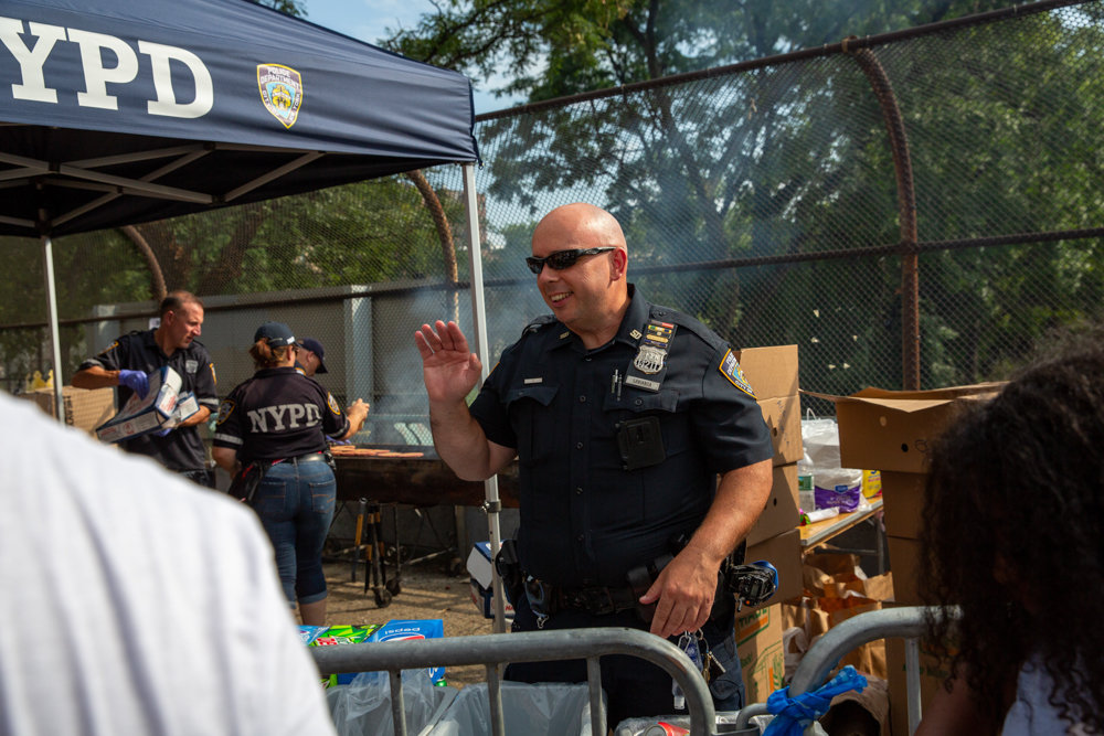 Officer John Labianca smiles and waves while on soda duty during the 50th Precinct's National Night Out event on West 234th Street between Bailey Avenue and Broadway.
