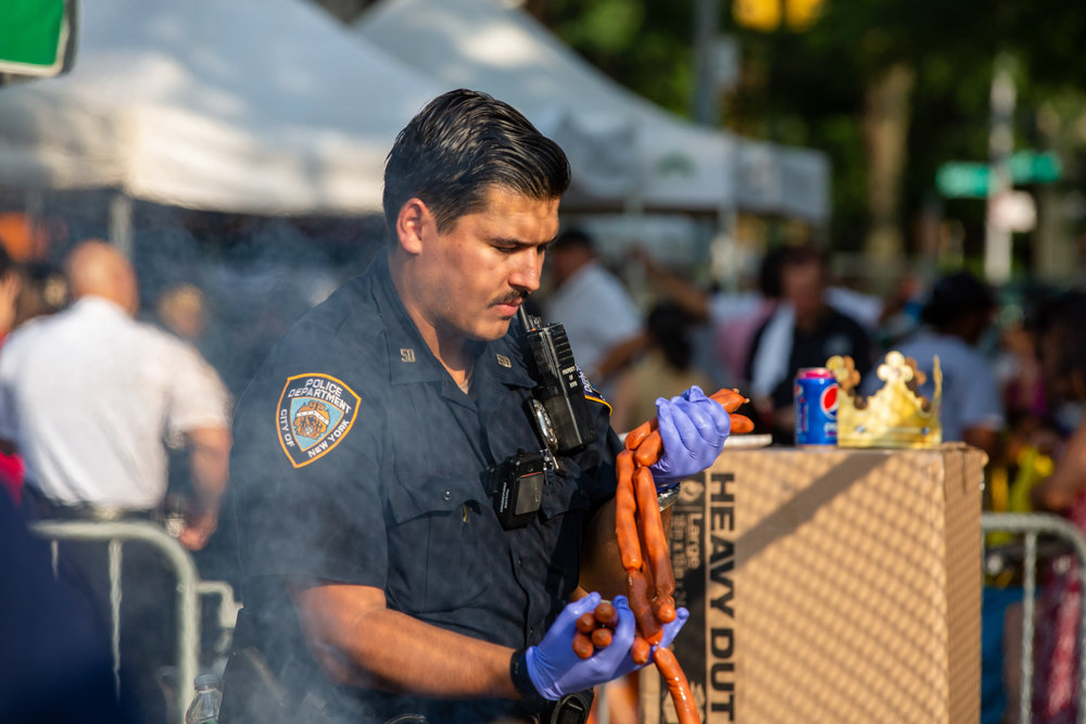 Officer Klaudio Rroku prepares to grill hot dogs for the 50th Precinct's National Night Out event.