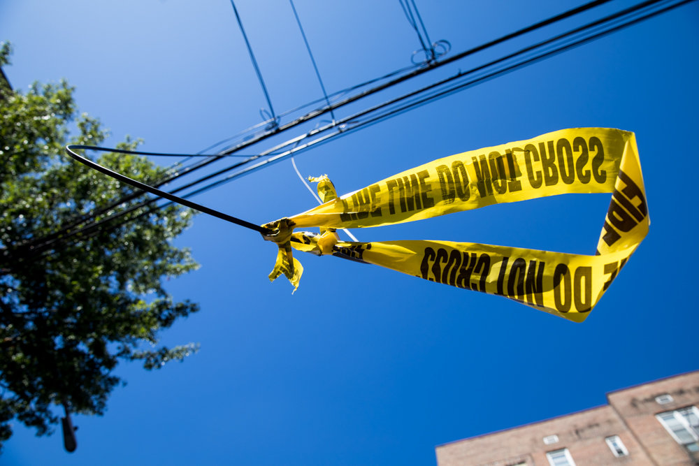 Yellow tape affixed to a stretch of wire hanging precariously close to the ground on Blackstone Avenue. Even though a call was put in to 311 several months ago, the problem has yet to be resolved.