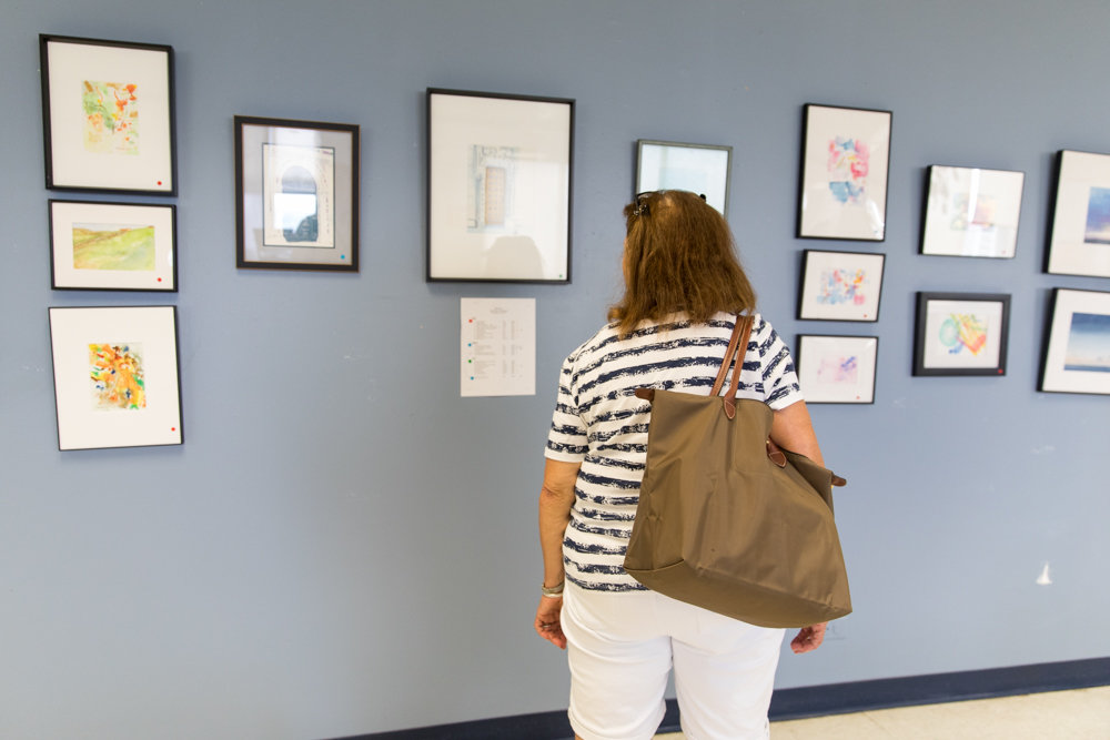 A visitor to RSS-Riverdale Senior Services looks at an exhibition of paintings by Ruth Hurd. The senior center is celebrating its 45th anniversary.