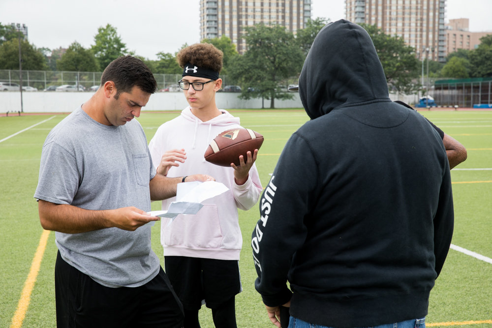 Clinton football coach John Applebee looks a doctor's note prior to a recent practice. The Governors look to rebound from a winless 2018 campaign in their first season in the PSAL's Bowl Conference.
