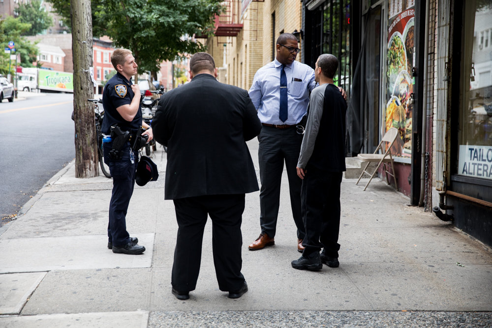 Law enforcement officials speak with Ismael's Gourmet Deli owner Ismael Diaz, right, while responding to a string of burglaries at three businesses on West 238th Street and Bailey Avenue.