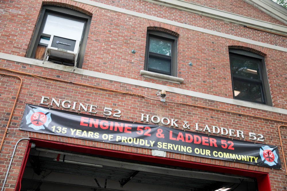 A banner celebrating the 135th anniversary of Engine and Ladder 52 hangs over the entrance to the Riverdale firehouse.