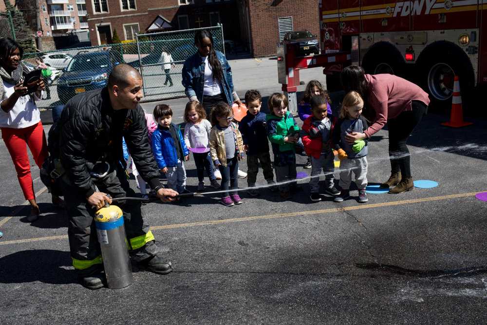 Jeff Espreo, a firefighter with Ladder 52, sprays water — much to the delight of students from Bedrock Preschool — during a visit to the school last year. Engine 52 celebrates its 135th anniversary this year.
