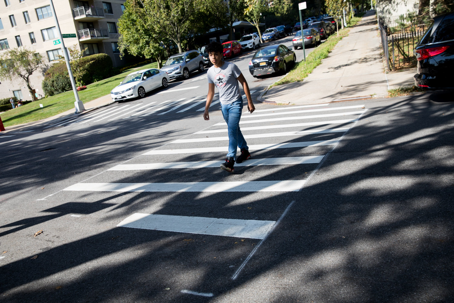 A pedestrian crosses at the intersection of Hudson Manor Terrace and West 236th Street. The city's transportation has endeavored to make the intersection safer for pedestrians through the removal of some parking spots, which has angered neighborhood drivers.