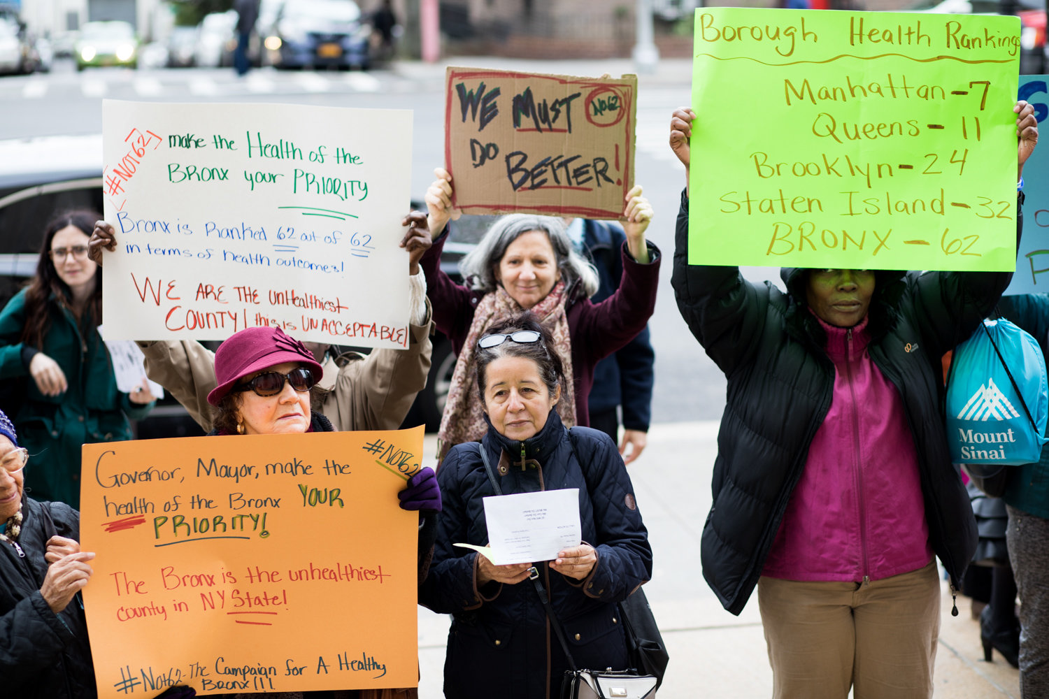 People hold signs at a rally last year highlighting the fact that the Bronx ranks last in the County Health Rankings and Roadmaps Report, a joint effort by the University of Wisconsin and the Robert Wood Johnson Foundation to measure how health is influenced by where people live.