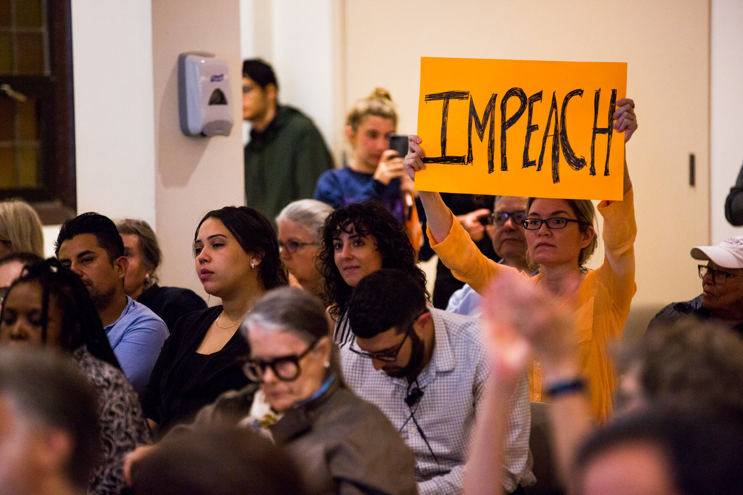 Stephanie Fitzhugh holds up a sign that reads 'impeach' at a Washington Heights forum about the impeachment process hosted by U.S. Rep. Adriano Espaillat on Oct. 7.