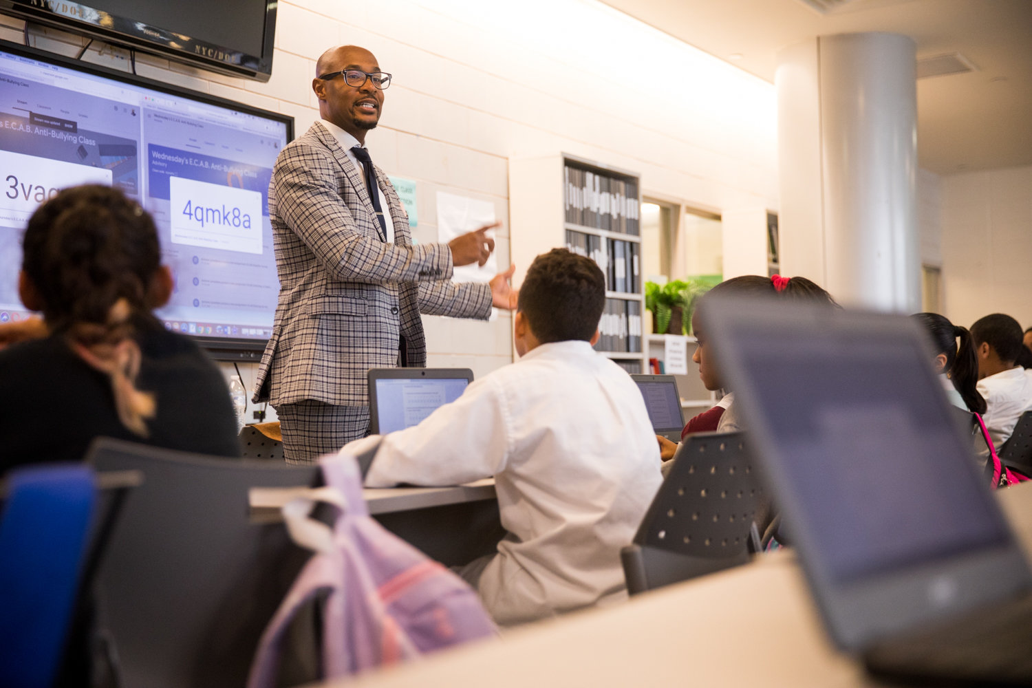 Antoine Larosiliere, a sixth-grade teacher at IN-Tech Academy, guides students through surveys during Empowering Communities Against Bullying, an after-school anti-bullying workshop he inaugurated last year.