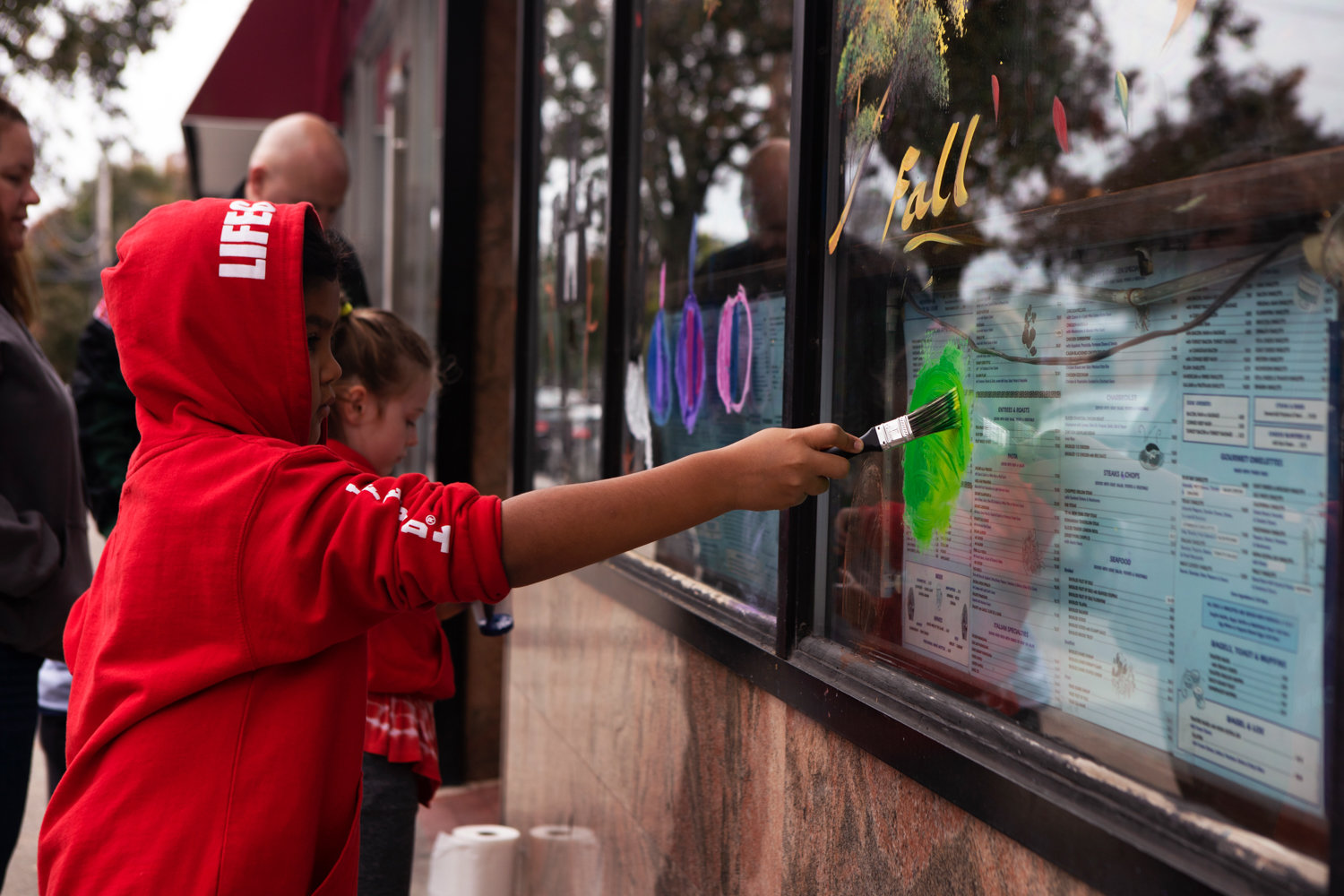 Children paint the windows outside Blue Jay Restaurant on Johnson Avenue during the Kiwanis Club's annual Halloween window painting contest.