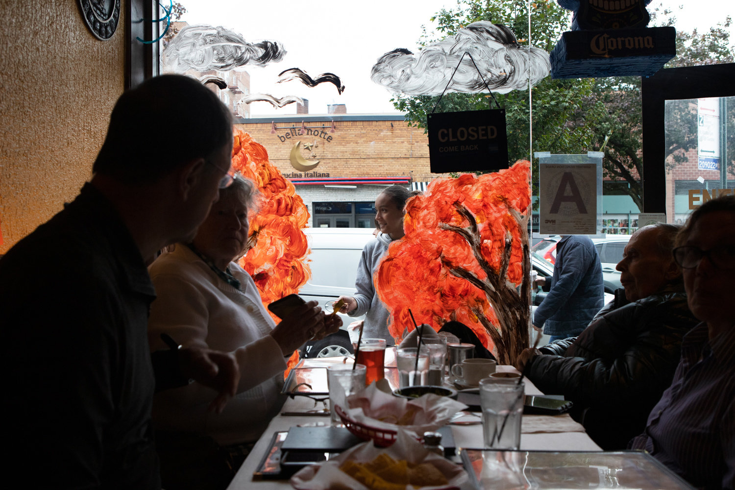 A family enjoys a meal at Metate while children paint the restaurant's windows during the Kiwanis Club's annual Halloween window painting contest.
