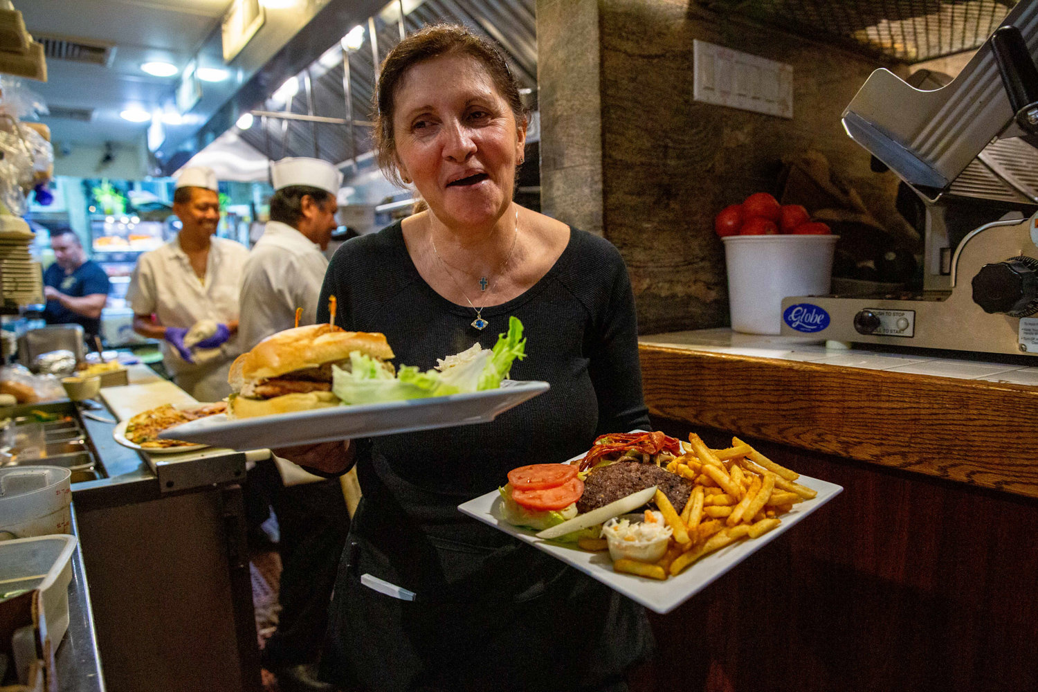 Pamela Liritsis, a familiar face to locals and regulars alike, carries freshly cooked cheeseburgers and fries, a classic diner staple, out of the kitchen to customers at Gold Mine Café on the corner of Broadway and West 231st Street.