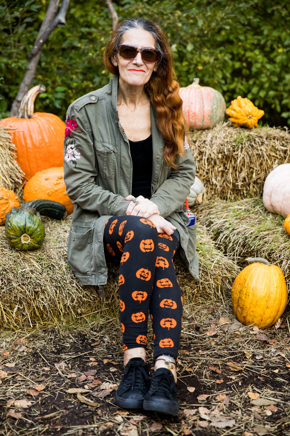 Irina Pilizota sits among multicolored gourds at the New York Botanical Garden. She makes a point to visit the Spooky Pumpkin Garden every year.