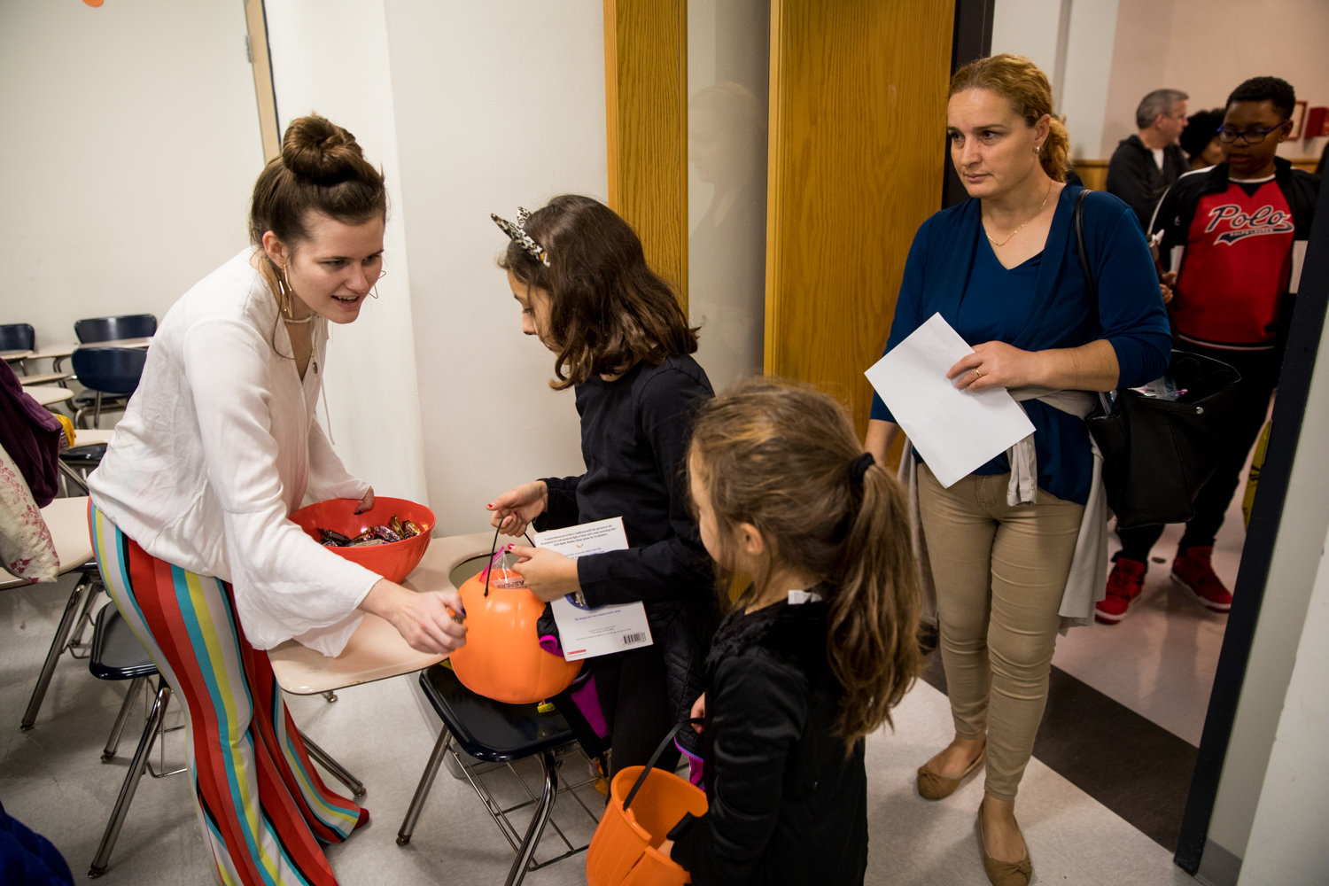 Manhattan College senior Mackenzie Kolman hands out candy to costumed children during the school's annual Safe Halloween event on Oct. 25.