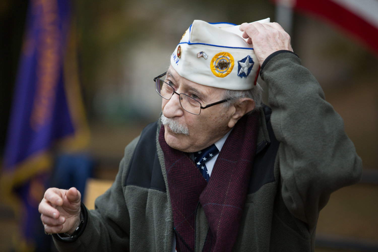 Herb Barret puts on his cap before opening the Veterans Day ceremony at Van Cortlandt Park's Memorial Grove in 2017. Barret first organized the ceremony in 2007 with his friend and fellow veteran Donald Tannen, who died in 2014.