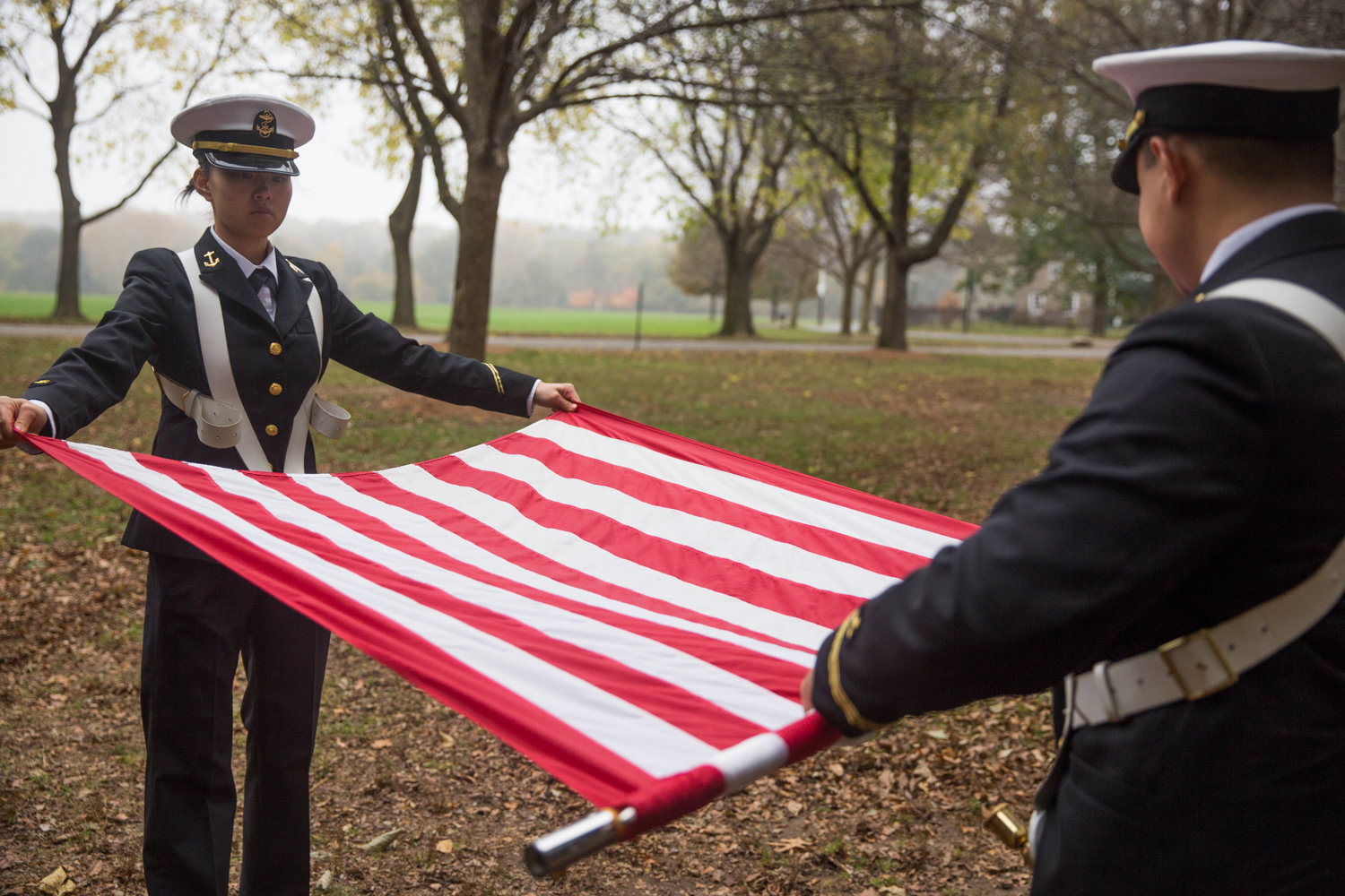 Members of the SUNY Maritime College Color Guard roll the flags after the presentation of colors at a Veterans Day ceremony at Memorial Grove in 2017.