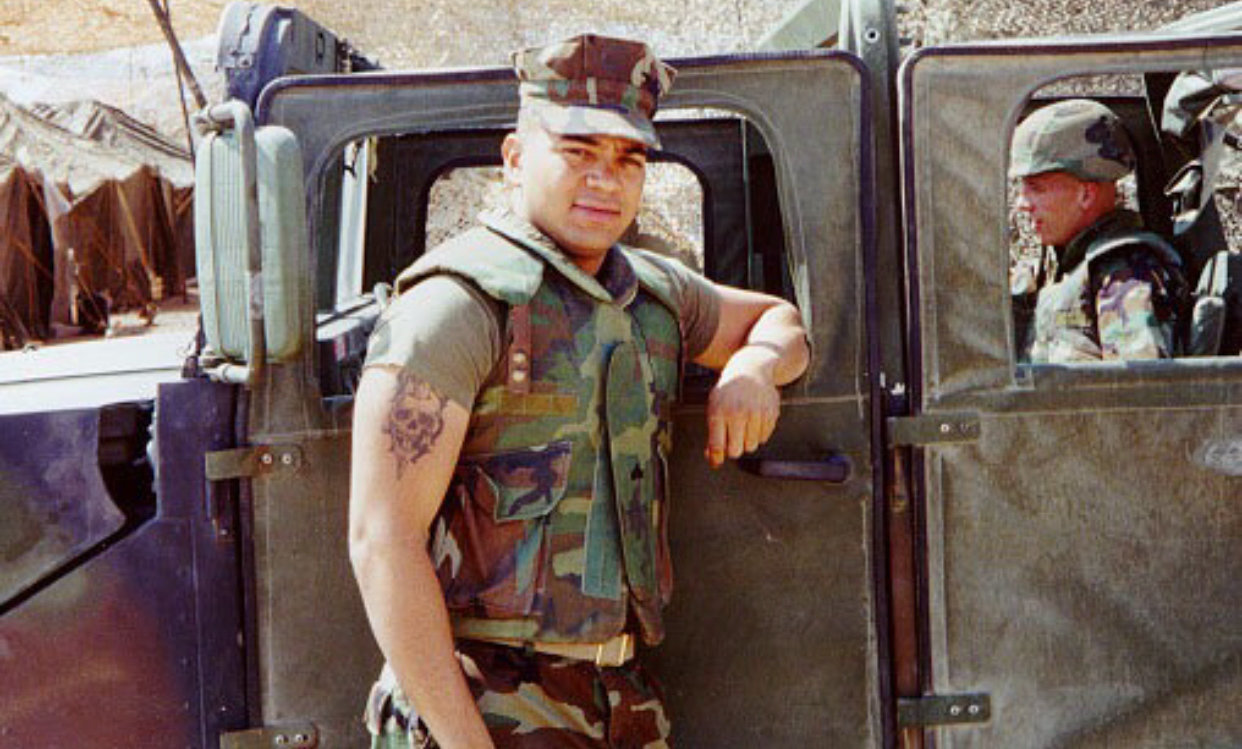A 2004 photograph shows Elio Acosta deployed as a Marine in Kuwait. Acosta is now studying photography at Lehman College.
