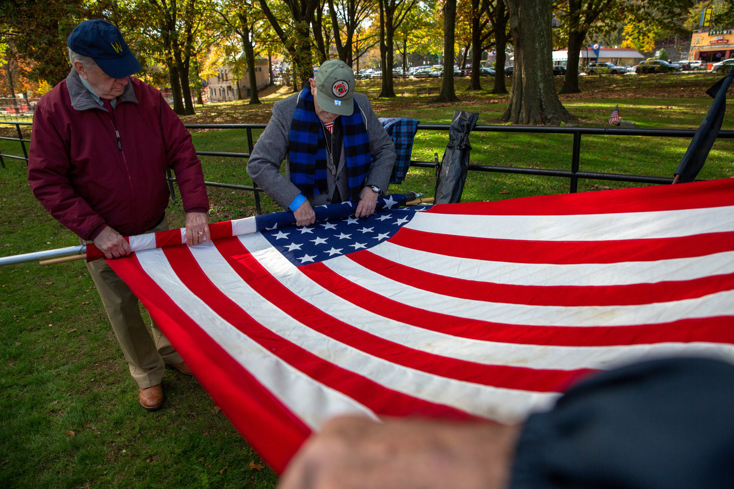 Herb Barret, right, helps roll up the American flag at the end of a Veterans Day ceremony in Van Cortlandt Park's Memorial Grove.