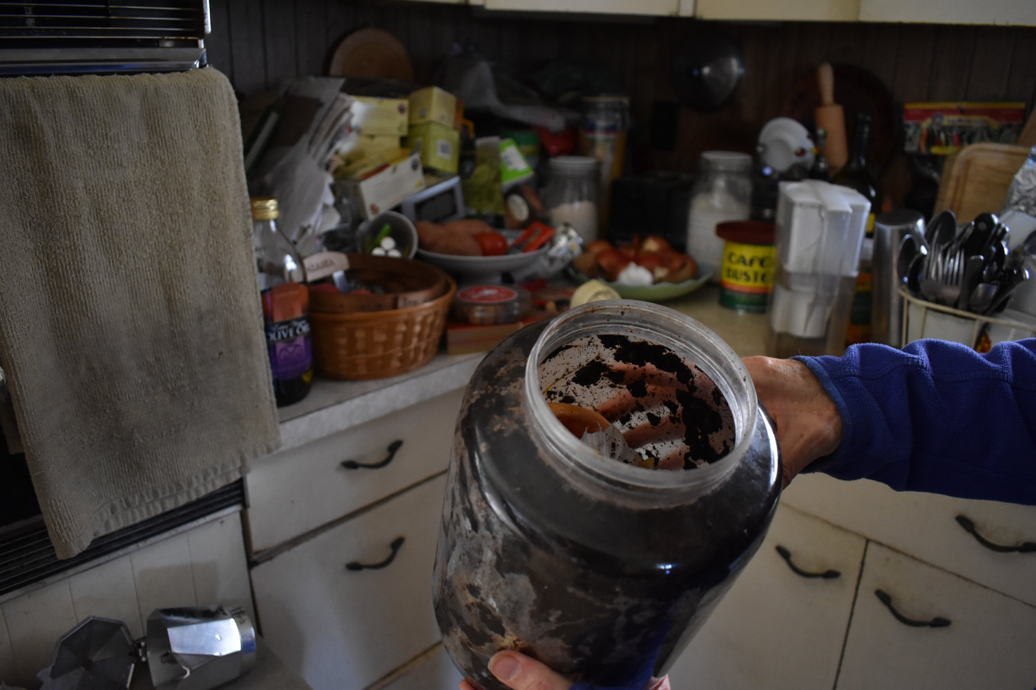 Debbi Dolan holds up a jar filled with compost inside her home. She uses compost throughout her garden.