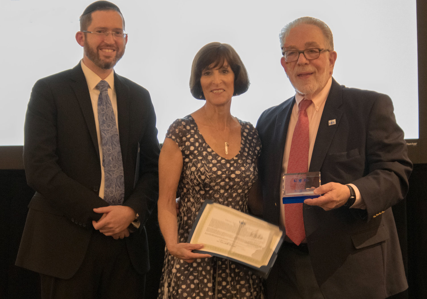 Karen Franklin smiles with her lifetime achievement award from the International Association of Jewish Genealogical Societies. She is joined by the organization's president, Ken Bravo, right, and board secretary Avraham Groll.