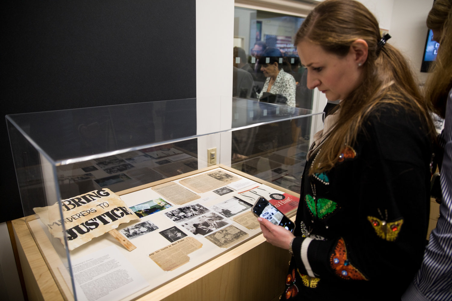 Visitors look at articles and signs protesting Boleslavs Maikovskis at the Herman and Lea Ziering Archive Collection.