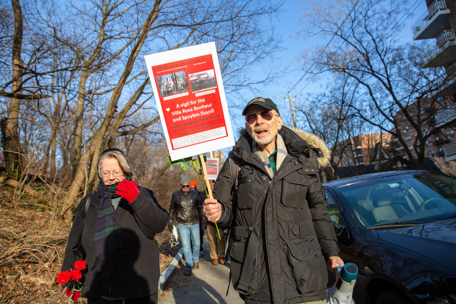Perry Brass, right, and Jennifer Scarlott lead a group of community members toward the Villa Rosa Bonheur for a vigil in support of the historic apartment building in February. Brass lives in the Villa Rosa's sister building, Villa Charlotte Bronte.