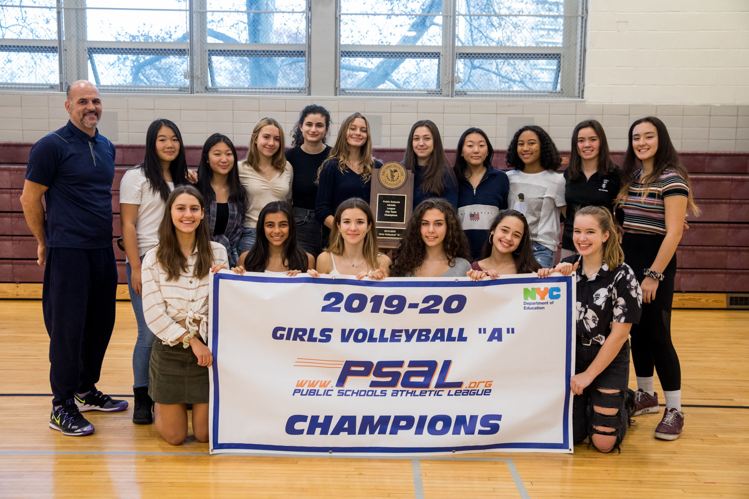 Bronx Science head coach Dan Skilins (upper left) and his Bronx Science girls volleyball team pose with their championship banner and trophy after the Wolverines defeated top-seeded Brooklyn Tech for their first PSAL city title.