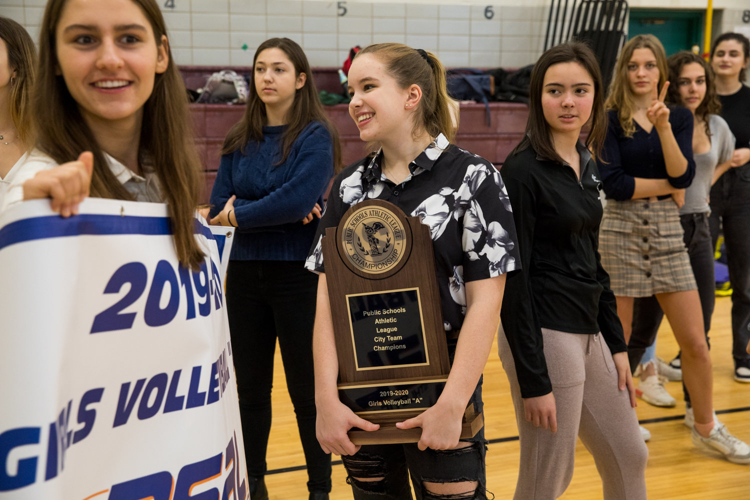 Darya Lollos drapes herself in the championship banner while Amanda Maeglin hugs the team trophy as the Bronx Science girls volleyball team celebrates its first PSAL city championship.