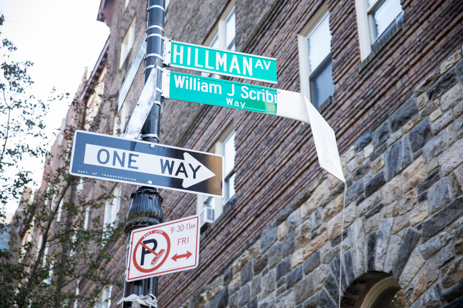 The sign for William J. Scribner Way is unveiled during a Nov. 15 ceremony. The corner of Hillman Avenue and Van Cortlandt Park South is named for the late founder of the Bronx Arts Ensemble, which is headquartered nearby.