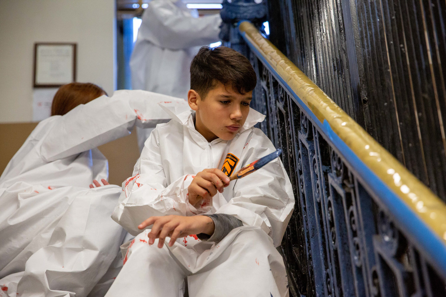 Logan Donato, son of Local Union No. 3 IBEW member Chris Donato, paints a banister inside the Kingsbridge Heights Community Center on Nov. 16. The union teamed up with Rebuilding Together NYC to fix up the center, including repainting, simple rewiring work and moulding replacement.