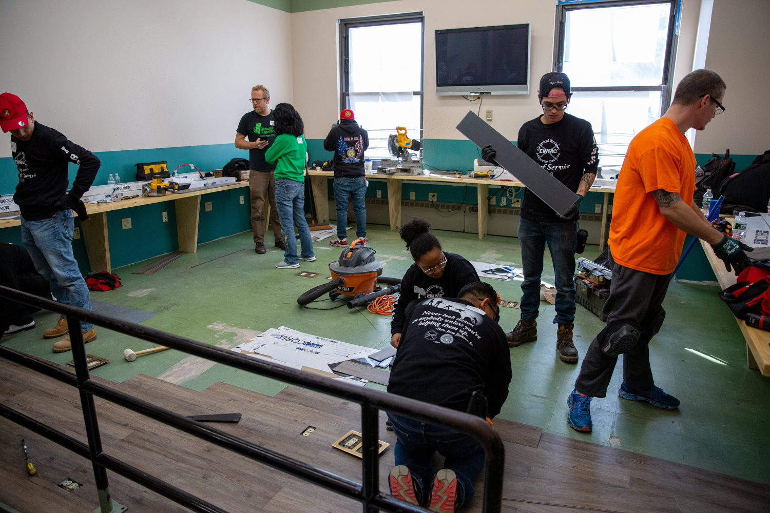 Volunteers from Rebuilding Together NYC and Local Union No. 3 IBEW resurface a classroom floor at the Kingsbridge Heights Community Center.