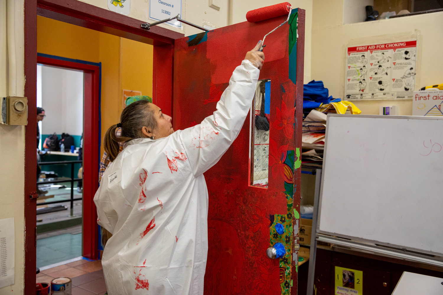 Anette Díaz Rivera, a business representative for Local Union No. 3 IBEW, paints a door in the Kingsbridge Heights Community Center.