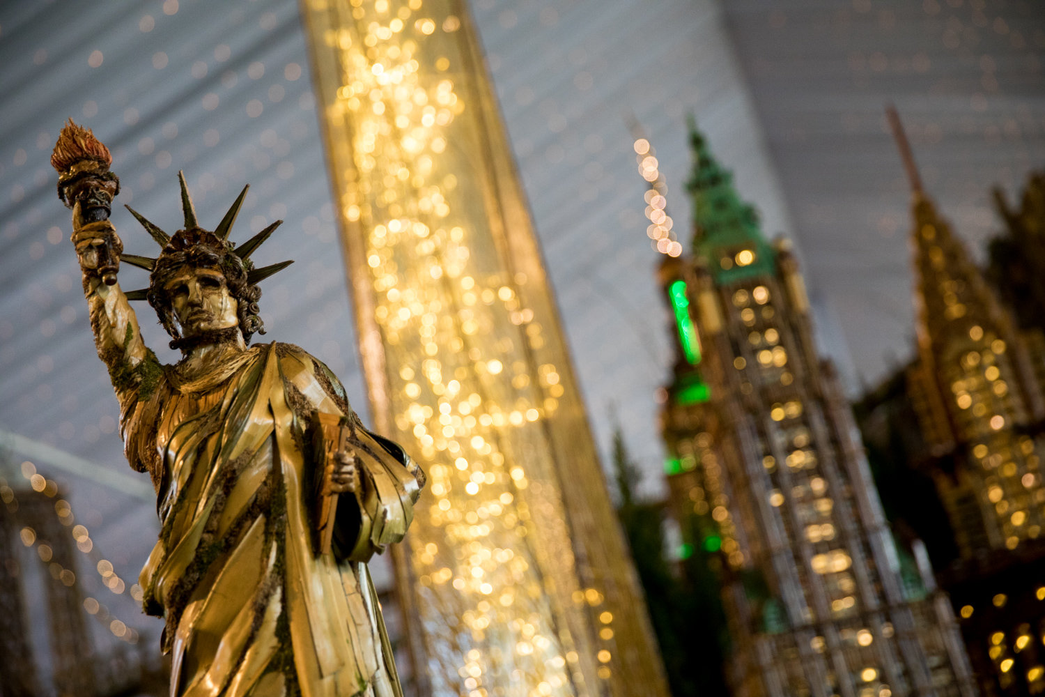 A replica of the Statue of Liberty stands in front of the skyline of Lower Manhattan in the Holiday Train Show at the New York Botanical Garden.
