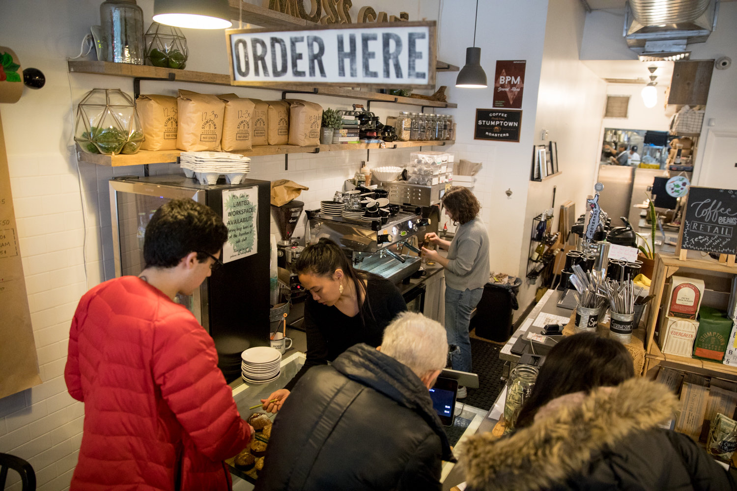 Customers place their orders at Moss Café on Johnson Avenue. With the new minimum wage law going into effect, owner Emily Weisberg looked to see where she could cut expenses to ensure she could pay her employees properly. Still, she recognizes that $15 an hour is not a living wage in New York City.