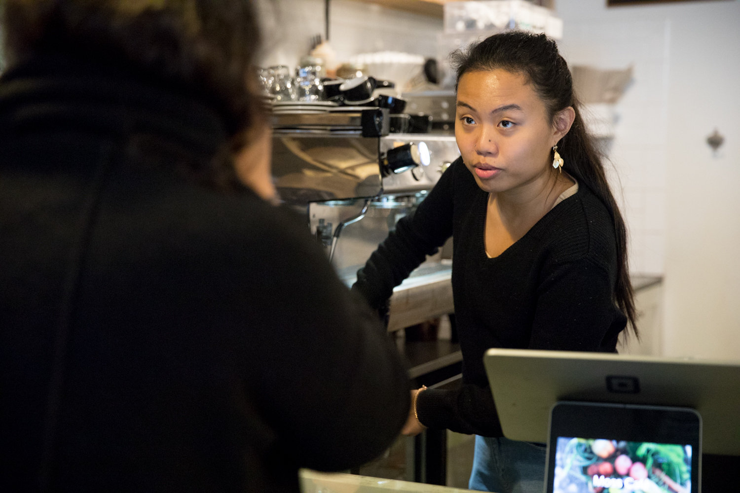Solange Rizon helps a customer at Moss Cafe. The Johnson Avenue eatery employs approximately 25 people, which means it's been subject to the $15 minimum wage since last year. Owner Emily Weisberg has looked to cut costs where possible to ensure her employees get paid properly.