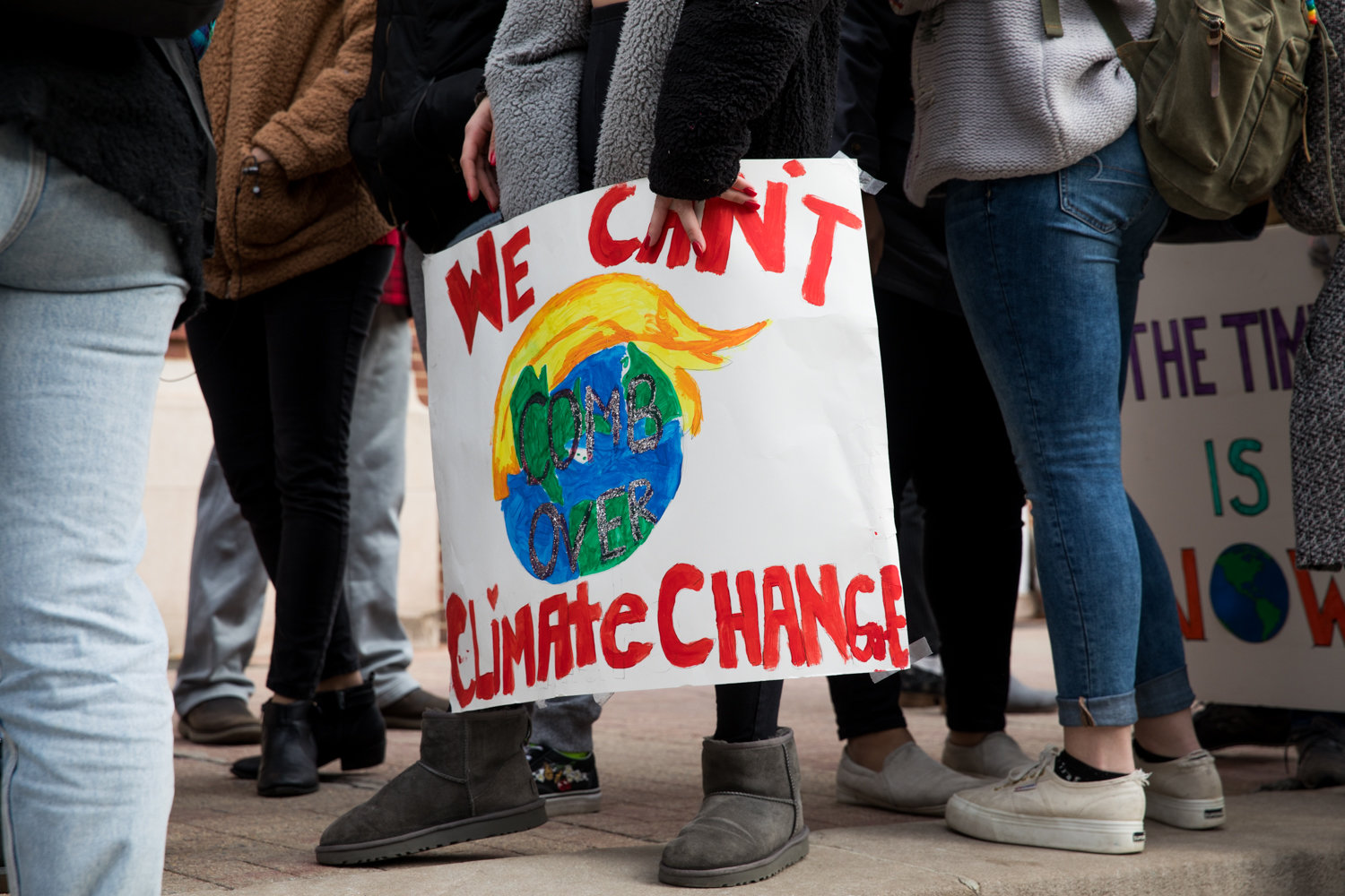 A Manhattan College student holds a sign reading 'We can't comb over climate change' during an awareness campaign between classes.