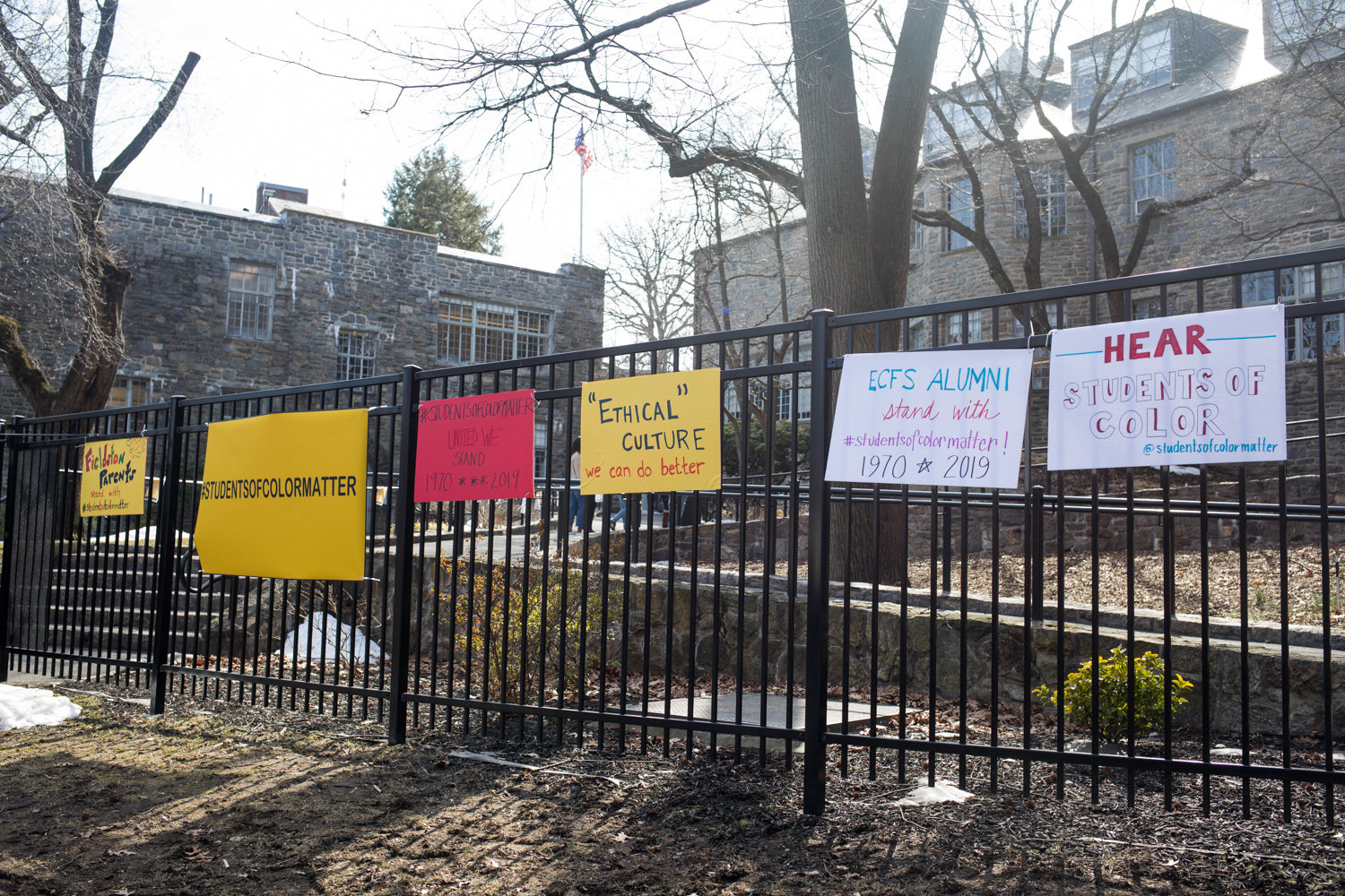 Signs expressing solidarity with the Students of Color Matter organization adorn a fence last year outside Ethical Culture Fieldston School. In the wake of a lawsuit over alleged systemic racism. Nearly a year later, the school is in the middle of another controversy following an outcry over a guest speaker's alleged anti-Semitic remarks. The school subsequently fired history teacher J.B. Brager, reportedly over social media posts in relation to that controversy.