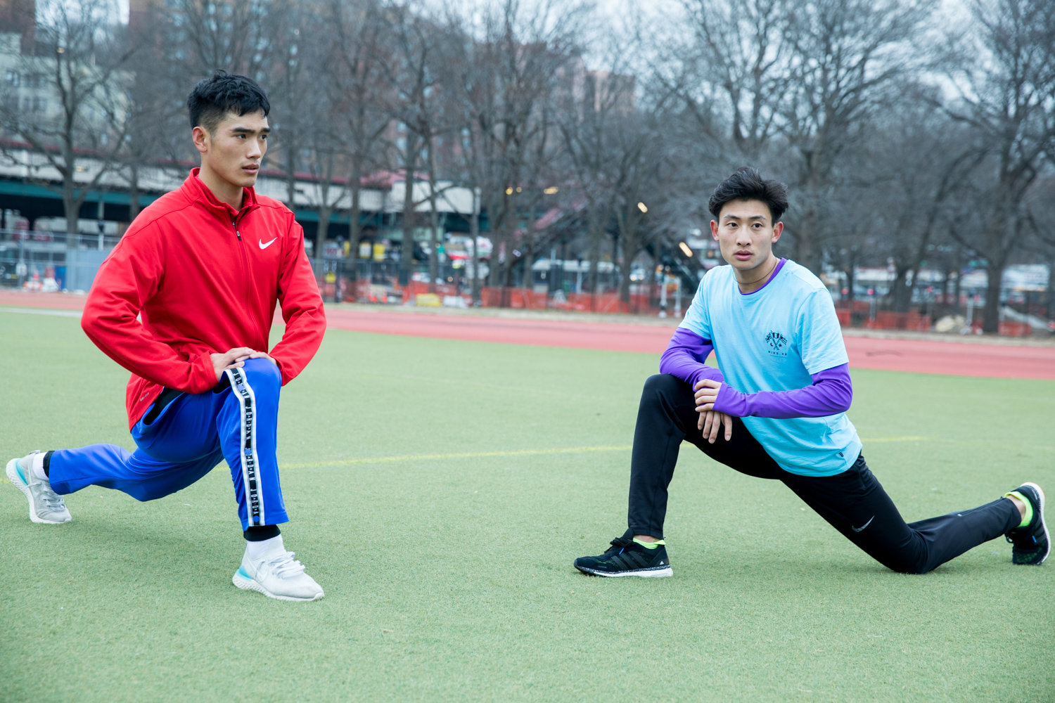 Meng Fanxu, left, and You Junjie stretch after running exercises with Manhattan College running coach Matt Centrowitz in Van Cortlandt Park.