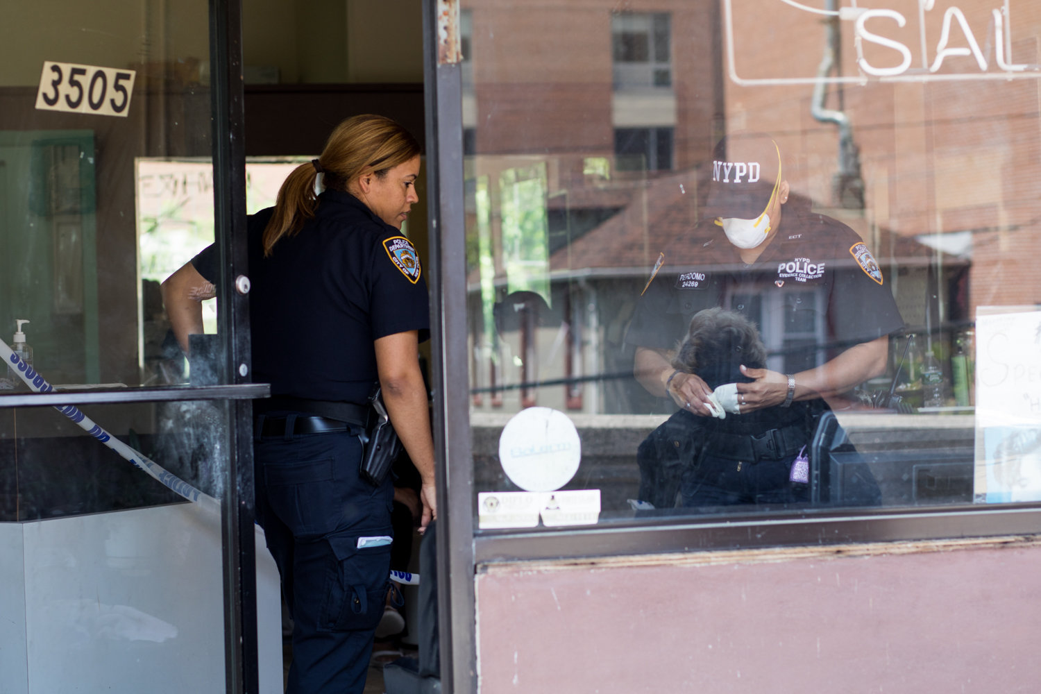Police officers investigate a crime scene at Park Terrace Unisex Salon on Riverdale Avenue, one of three businesses targeted by a robber in June 2018.
