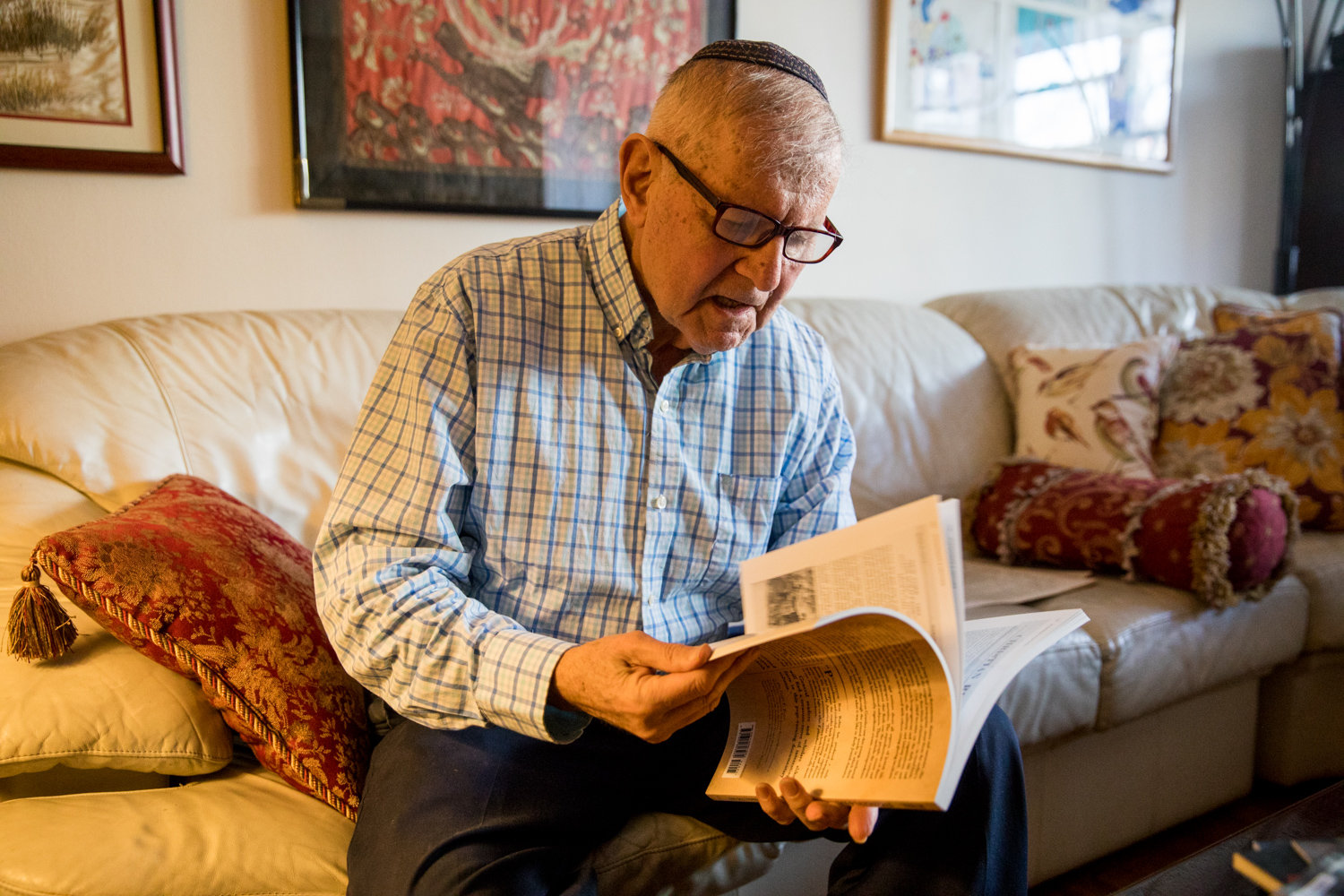 Ron Rubin looks through a copy of his book 'Strangers & Natives' in his Riverdale home. He put together a book based on old newspaper reports to tell the story of early Jewish life in the United States.