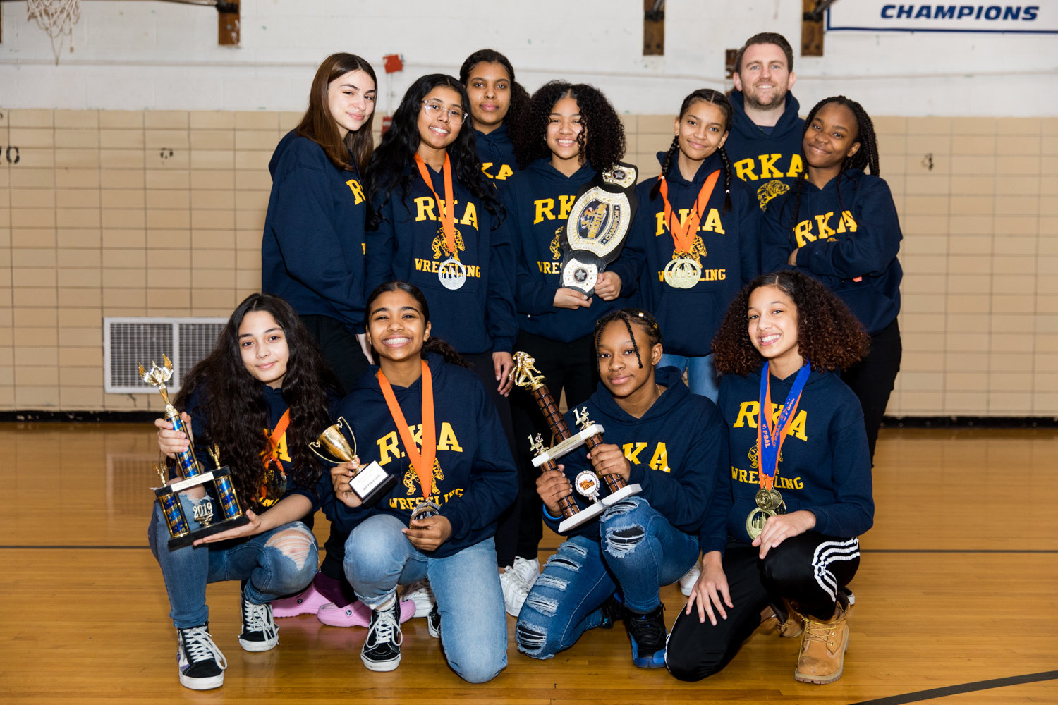 Riverdale/Kingsbridge Academy wrestling coach Michael Lepetit poses with some of his girls that have helped make the Tigers' middle and high school wrestling teams so successful.