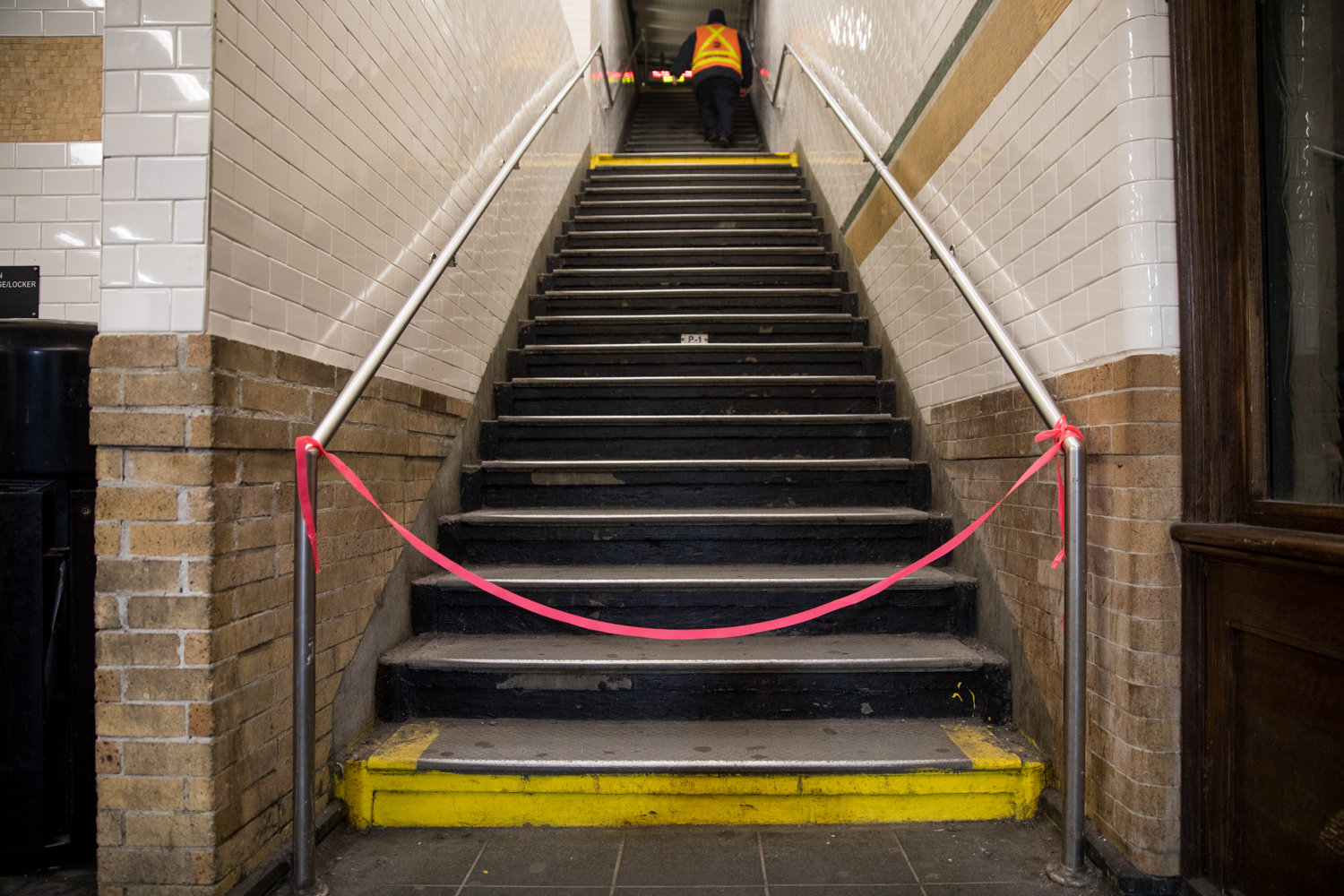 Red tape blocks entry to the stairs leading up to the downtown 1 train platform at the Dyckman Street station, where service is cut off between there and the 137th Street station.