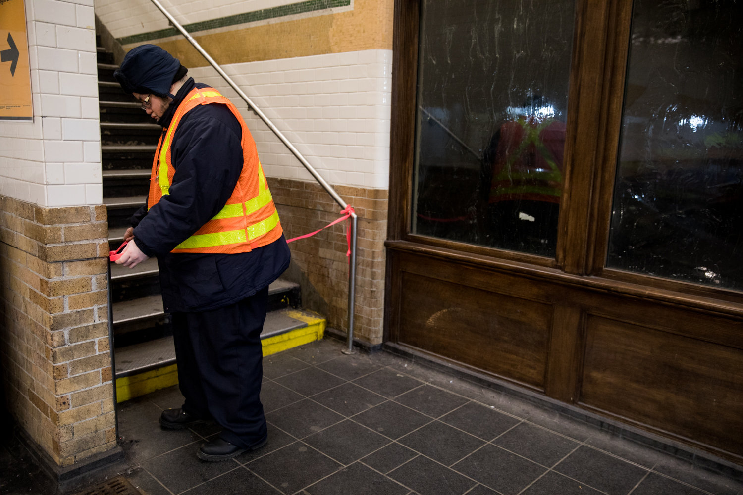 An MTA worker affixes red tape to the stairs leading up to the downtown platform at the Dyckman Street 1 train station after service is suspended between there and 137th Street.