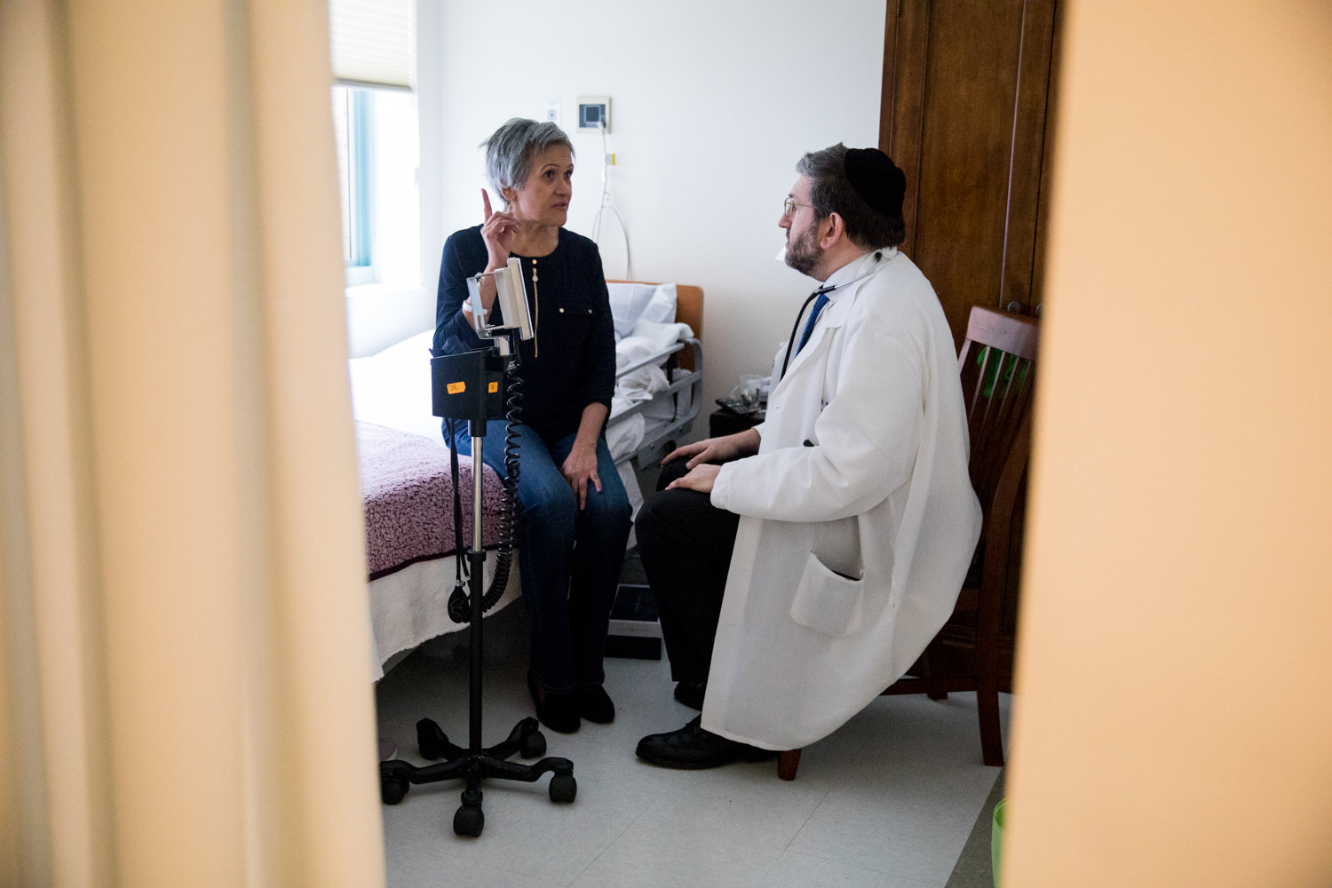Hebrew Home at Riverdale resident Maria Mejia talks with medical director Dr. Zachary Palace during a routine check-in. Palace and his team feel prepared regarding the current coronavirus because of their extensive experience dealing with infectious disease.