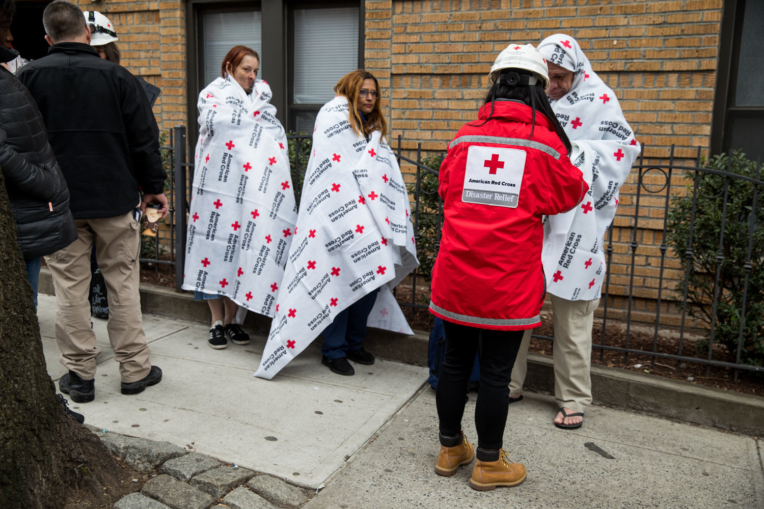 A member of the American Red Cross helps residents of 215 W. 242nd St., where a fire broke out Friday morning.
